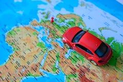 Ciérrese para arriba en una mano que coloca un perno en una marca del juguete del mapa y del coche adonde ir Imágenes de archivo libres de regalías