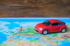 Ciérrese para arriba en una mano que coloca un perno en una marca del juguete del mapa y del coche adonde ir Fotos de archivo libres de regalías