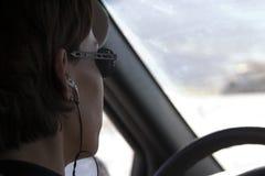 Ciérrese para arriba en una mujer que conduce con un receptor de cabeza encendido Foto de archivo libre de regalías