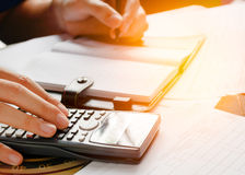 Ciérrese para arriba, hombre de negocios o contable del abogado que trabaja en cuentas usando una calculadora y que escribe en do Foto de archivo