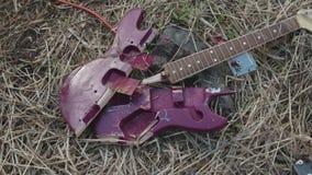 Ciérrese para arriba para la guitarra púrpura quebrada que miente en el heno marchitado, visión superior existencias Cubierta vio almacen de video