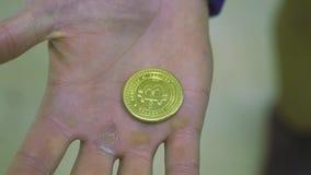 Ciérrese para arriba para la mano del hombre que sostiene la moneda del recuerdo del bitcoin en fondo borroso existencias Bitcoin almacen de video