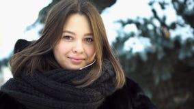 Ciérrese para arriba para la muchacha joven, atractiva en un abrigo de pieles y la bufanda hecha punto que mira derecho en un par imagen de archivo