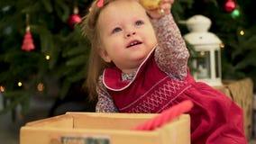 Ciérrese para arriba para la muchacha linda del niño con la bola de oro decorativa que se sienta cerca de árbol de los christmass almacen de video