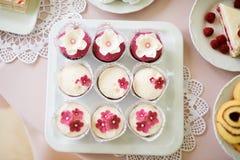 Ciérrese para arriba, las magdalenas en la bandeja adornada con las flores rosadas Foto de archivo