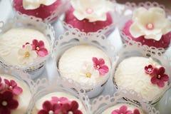 Ciérrese para arriba, las magdalenas en la bandeja adornada con las flores rosadas Fotografía de archivo libre de regalías