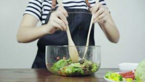 Ciérrese para arriba mujer joven consciente de la salud de la principal que lanza una ensalada verde orgánica sabrosa almacen de video