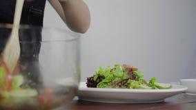 Ciérrese para arriba mujer joven consciente de la salud de la principal que lanza una ensalada verde orgánica sabrosa almacen de metraje de vídeo