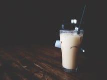 Ciò è tè ghiacciato tailandese nel vetro sopra lo scrittorio di legno, il tono morbido immagine stock libera da diritti