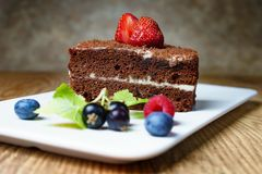 Ciò è un dolce delizioso della crema del cioccolato, con le fragole, il ribes nero ed i mirtilli freschi Su un fondo marrone deli fotografia stock