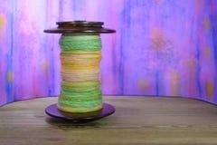 Ciò è una bobina della ruota di filatura riempita di filato della mano Immagini Stock Libere da Diritti