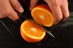 Ciąć świeżej pomarańcze z nożem Fotografia Royalty Free