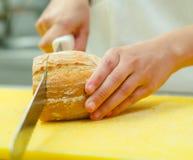 Ciąć plasterki od bochenka chleba obsiadanie na kolor żółty powierzchni, ręki mienia ampuły nóż Zdjęcie Royalty Free
