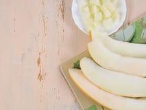Ciąć soczystych melonów plasterki na białym talerzu i melon Obrazy Royalty Free