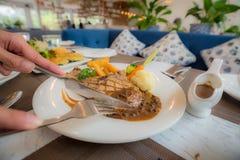 Ciąć stek nożem w białym naczyniu podczas gdy bierze gościa restauracji obraz stock