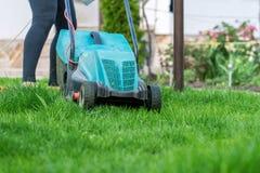 Ciąć trawy z elektrycznym gazonu kosiarzem Zdjęcie Royalty Free
