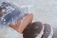Ciący czekoladowego ciasto dla tortów z nożem na tle drewniana deska kropiąca z pszeniczną mąką obrazy stock