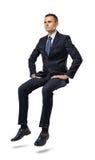 Ciący pełny portret biznesmena obsiadanie na niewidzialnej powierzchni Fotografia Stock
