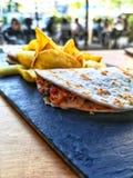 Ciągnący wieprzowiny tacos ściska z dłoniakami na czarnym talerzu ludzie w tle zdjęcia royalty free