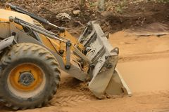 Ciągnik buldożer wiosłuje piasek i dorówna fotografia royalty free