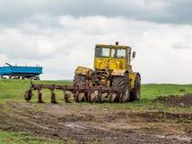 Ciągnik orze ziemię w polach w wiośnie Obrazy Stock