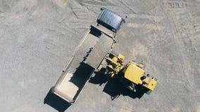 Ciągnik stawia żwir w plecy ciężarówka w odgórnym widoku zbiory
