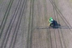 Ciągnik z zależącym od systemem opryskiwanie pestycydy Nawożący z ciągnikiem, w postaci aerosolu na polu zima, fotografia royalty free