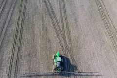 Ciągnik z zależącym od systemem opryskiwanie pestycydy Nawożący z ciągnikiem, w postaci aerosolu na polu zima, zdjęcie royalty free