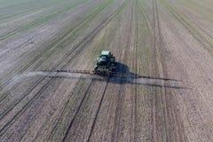 Ciągnik z zależącym od systemem opryskiwanie pestycydy Nawożący z ciągnikiem, w postaci aerosolu na polu zima, obraz stock