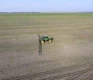 Ciągnik z zależącym od systemem opryskiwanie pestycydy Nawożący z ciągnikiem, w postaci aerosolu na polu zima w, zdjęcie royalty free