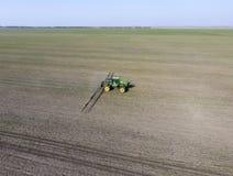 Ciągnik z zależącym od systemem opryskiwanie pestycydy Nawożący z ciągnikiem, w postaci aerosolu na polu zima w, obrazy royalty free
