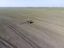 Ciągnik z zależącym od systemem opryskiwanie pestycydy Nawożący z ciągnikiem, w postaci aerosolu na polu zima w, obraz royalty free