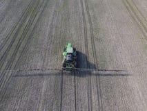 Ciągnik z zależącym od systemem opryskiwanie pestycydy Nawożący z ciągnikiem, w postaci aerosolu na polu zima w, obrazy stock