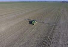 Ciągnik z zależącym od systemem opryskiwanie pestycydy Nawożący z ciągnikiem, w postaci aerosolu na polu zima w, zdjęcia royalty free