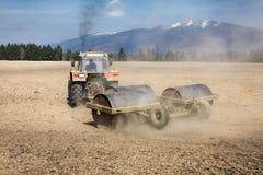Ciągnikowy ciągnięcie ciężkiego metalu rolownik na suchym polu, pył behind i fotografia stock