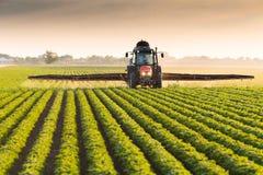 Ciągnikowy opryskiwanie soi pole przy wiosną fotografia stock