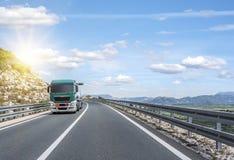 Ciężarówka śpieszy się wzdłuż drogi na zewnątrz miasta, przeciw tłu zmierzch i góry Obrazy Stock