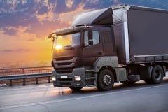 Ciężarówka iść na autostradzie na zmierzchu obraz stock