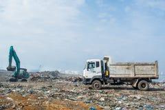 Ciężarówka i buldożer przy śmieciarskim usypem pełno dym, ściółka, klingeryt butelki, banialuki i grat przy tropikalną wyspą, fotografia stock