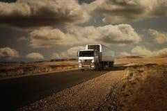 Ciężarówka podróżuje na drodze w pustyni przy zmierzchem Obrazy Royalty Free