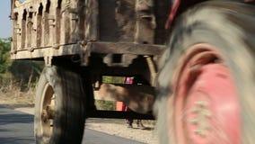 Ciężarówka z ludźmi przechodzi w dół drogę podczas gdy kobiety chodzą na boku zbiory