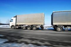 Ciężarówka z przyczepy jeżdżenia postem na zimy wsi drodze z śniegiem przeciw niebieskiemu niebu zdjęcie royalty free