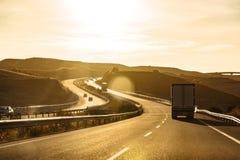 Ciężarówki i samochodów jeżdżenie na autostradzie przy zmierzchem zdjęcia royalty free