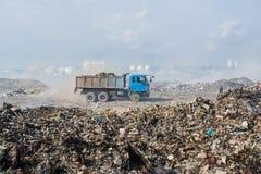 Ciężarówki jazda przy śmieciarskim usypem pełno dym, ściółka, klingeryt butelki, banialuki i grat przy tropikalną wyspą, zdjęcie royalty free