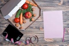 Ciężar strata i zdrowy łasowania pojęcie Otwarty pizzy pudełko z surowymi warzywami w nim, kuchni skale, pomiarowa taśma i papier obrazy stock