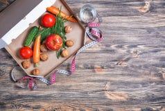 Ciężar strata i zdrowy pojęcie łasowania lub dieting Otwarty pizzy pudełko z surowymi warzywami w nim na drewnianym tle obrazy stock