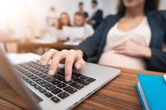 Ciężarna atrakcyjna kobieta pisać na maszynie na laptop klawiaturze Brzemienność przy miejscem pracy zdjęcia royalty free