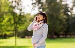 Ciężarna azjatykcia kobieta dzwoni na smartphone przy parkiem Obrazy Royalty Free