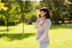 Ciężarna azjatykcia kobieta dzwoni na smartphone przy parkiem Zdjęcia Stock