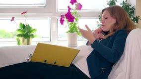 Ciężarna biznesowa kobieta opowiada na telefonu i kciuka falcówce z dokumentami zbiory wideo